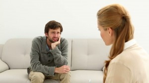 stock-footage-young-man-sitting-on-sofa-talking-to-his-therapist-at-therapy-session